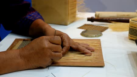 bamboo basket : Side view of hands of artisan craftsman elderly woman working weaving bamboo strips to make ancient handmade handcraft woven traditional Thai Khit or Khid pattern