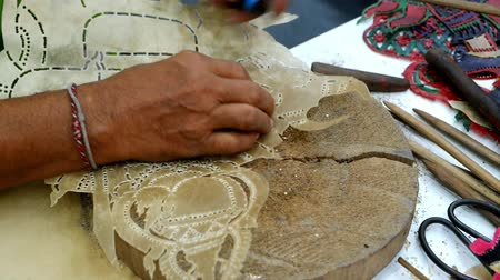 скрывать : Bangkok,Thailand. Jan 31,2020 : Hands of Thai professional artisan craftsman using tool carving buffalo hide or cowhide leather making traditional handmade handcraft perforated Nang Talung artwork