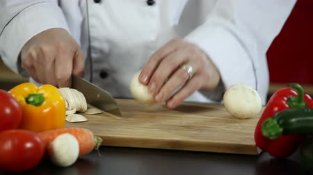 kesme tahtası : Video of a chef slicing mushrooms on a wooden cutting board in a restaurant kitchen.