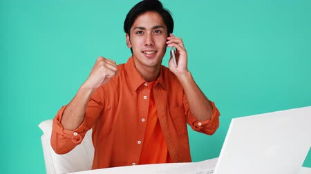 Picture of a Asian man making victory holding cell phone.