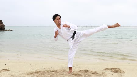pacific islands : Young man practicing karate at beach