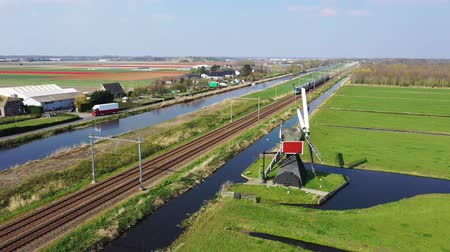 голландский : Aerial view of high speed train passing by traditional Dutch windmill, Netherlands, Holland