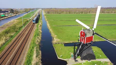 Aerial view of high speed train passing by traditional Dutch windmill, Netherlands, Holland