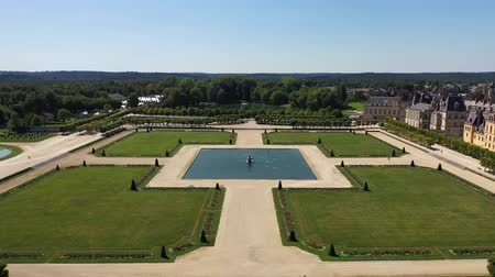 múlt : Aerial view of medieval landmark royal hunting castle Fontainbleau near Paris in France and lake with white swans