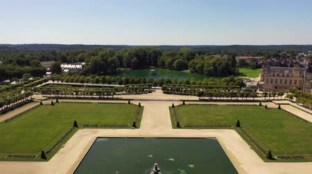 surroundings : Aerial view of medieval landmark royal hunting castle Fontainbleau near Paris in France and lake with white swans
