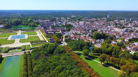 Aerial view of medieval landmark royal hunting castle Fontainbleau and lake with white swans, France