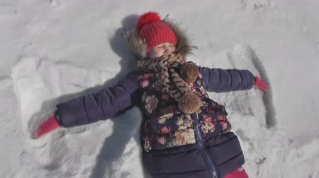 snow angel : girl makes a butterfly in the snow, winter weather Stock Footage
