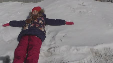 snow angel : The child fell on the snow and making dark hands and feet