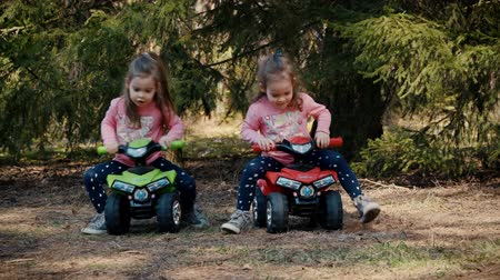 quads : Two little girls raced on toy quads in the woods in the summer Stock Footage