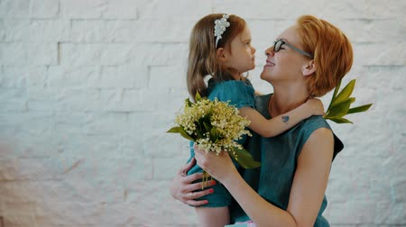 den matek : Mother and little daughter hug each other with flowers and a gift in their hands