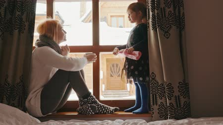 talc : woman is sitting by the window and talking with her daughter in a winter house