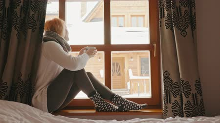 питьевой : woman with a mug of tea looks out of the window in winter Стоковые видеозаписи