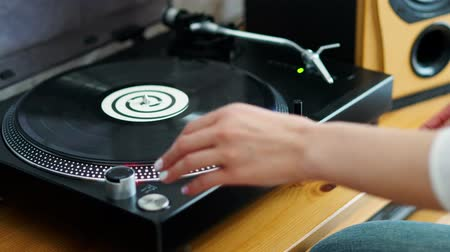 rock album : woman turns off the turntable takes the LP and finishes listening to music