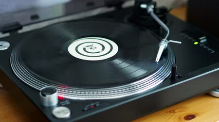 vinil : old vinyl record is spinning on a black turntable with a silver needle