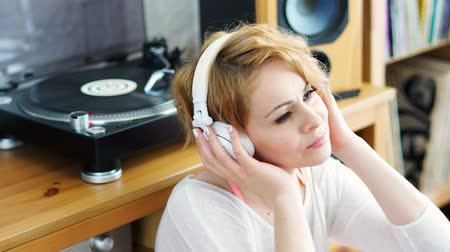 gramophone : beautiful woman sitting next to a turntable with headphones