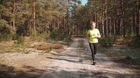 cross country : woman in a sports outfit runs through a beautiful summer forest