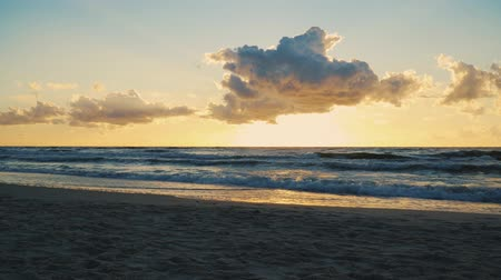 heavenly : sunset behind clouds over sea waves and sandy beach in summer