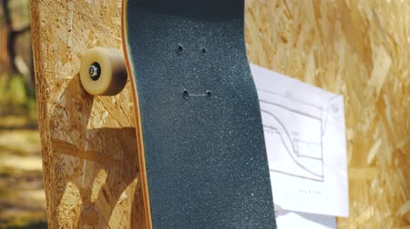 skateboard deck : view of a new skateboard on a wooden background with plans for a miniramp in a skatepark in the summer