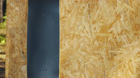skateboard deck : view of a new skateboard on a wooden background at a skatepark in the summer Stock Footage