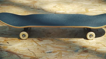 skateboard deck : view of a new skateboard with white wheels on a wooden background in a skatepark in the summer
