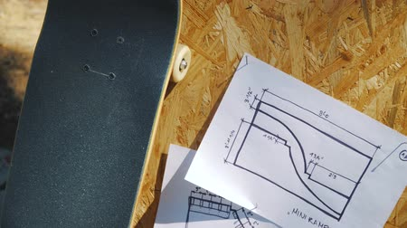 bruslař : view of a new skateboard on a wooden background with plans for a miniramp in a skatepark in the summer