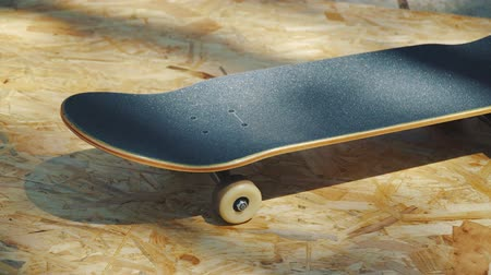 usado : view of a new skateboard with white wheels on a wooden background in a skatepark in the summer