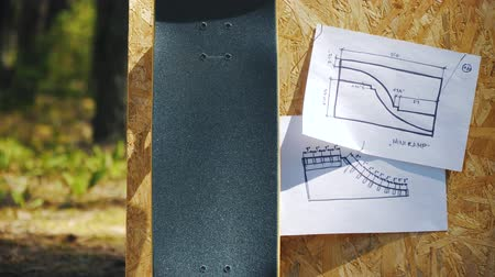 objeto : view of a new skateboard on a wooden background with plans for a miniramp in a skatepark in the summer