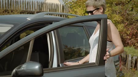 entering : young woman in a white T-shirt approaches the car opens the door and gets on Stock Footage