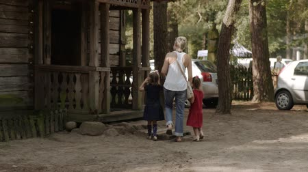 przedszkolak : young mother walks with her daughters in a rural park and watches old houses