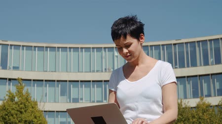переписка : young business woman in a white T-shirt sitting in front of an office building and working on a computer
