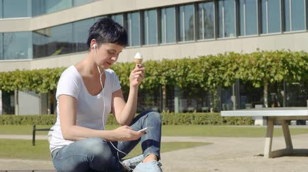 půvabný : young business woman in with icecream sits in front of an office building and listens to music on the phone