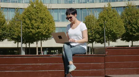 yazışma : young business woman in a white T-shirt sitting in front of an office building and working on a computer