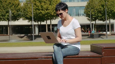 connectivity : young business woman in a white T-shirt sitting in front of an office building and working on a computer