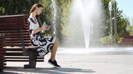 water display : young business woman in a dress sitting on a bench drinking water and working on the tablet