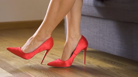 embellished : Woman on couch in red high heels crosses sexy and slim long legs Stock Footage