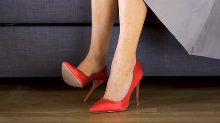 high heels : Woman on couch in red high heels crosses sexy and slim long legs Stock Footage