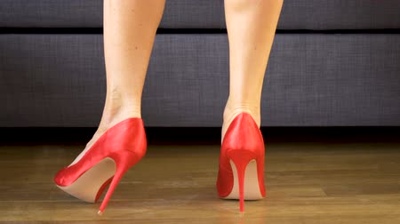 vysoký : Woman walks sensually in red high heels showing sexy and slim long legs