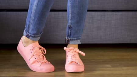 Woman standing by the sofa and showing her legs in comfortable coral sneakers Стоковые видеозаписи
