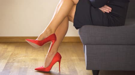 Woman on couch in red high heels crosses sexy and slim long legs Стоковые видеозаписи