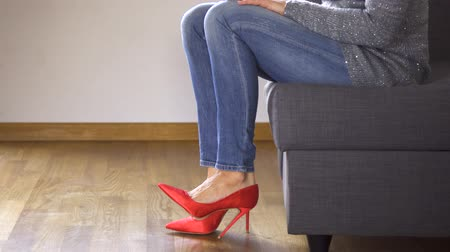 Woman on couch in red high heels shows and crosses sexy and slim long legs