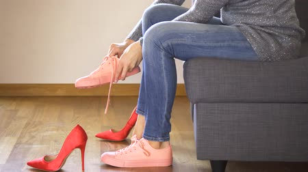 Slim woman in jeans on couch takes off sexy red heels and puts on coral sneakers