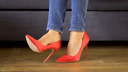 moda : Woman on couch in red high heels shows and crosses sexy and slim long legs