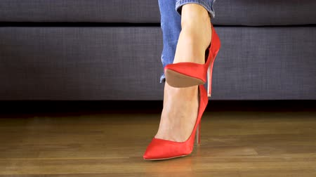 footgear : Woman on couch in red high heels shows and crosses sexy and slim long legs