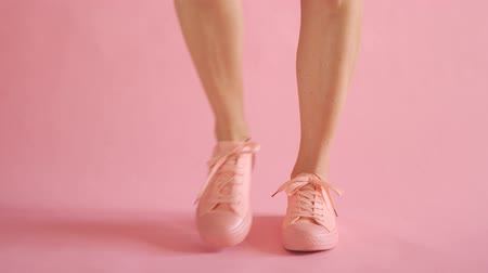 Close up of slim female legs dancing in sneakers on coral background