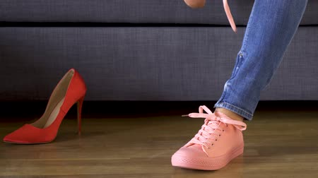 woman in jeans takes off sexy red heels and puts on comfortable coral sneakers