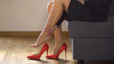 протирать : Beautiful sexy business woman takes off red high heels and massages painful legs