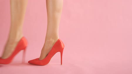 Close-up of shapely female legs walking in sexy high hells on coral background