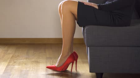 embellished : Woman on couch in red high heels shows and crosses sexy and slim long legs