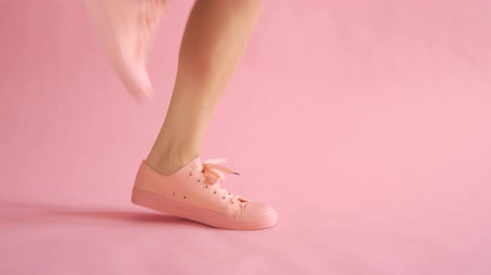 Close up of shapely female legs while running in sneakers on coral background