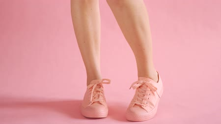 Close up of shapely female legs walking in sneakers on coral background